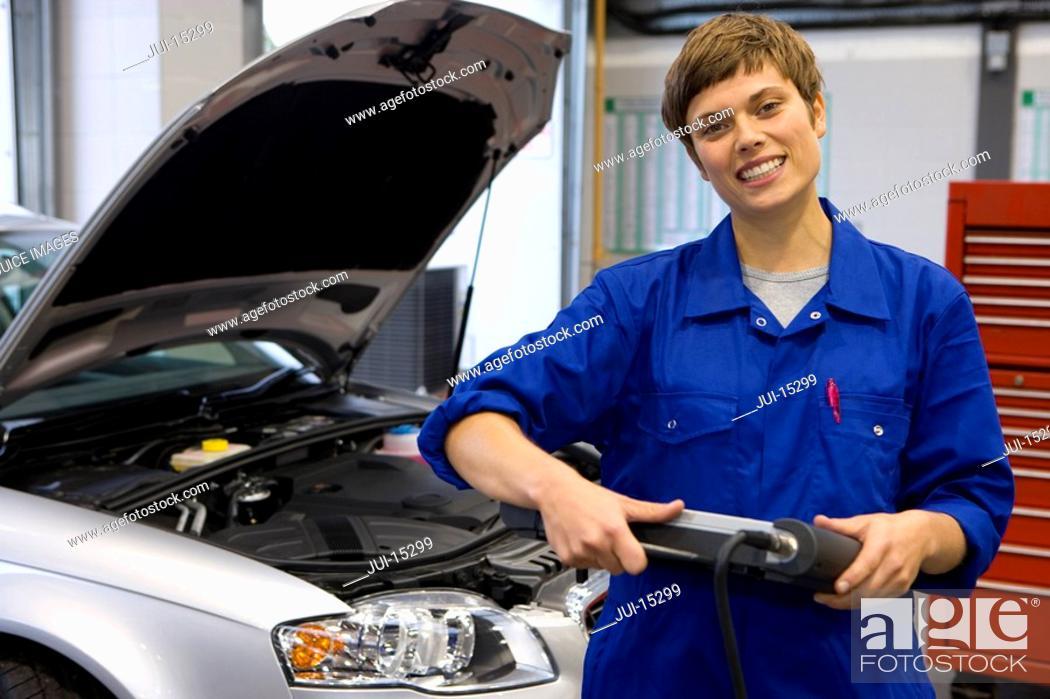Stock Photo: Female mechanic with electronic diagnostics device, portrait.