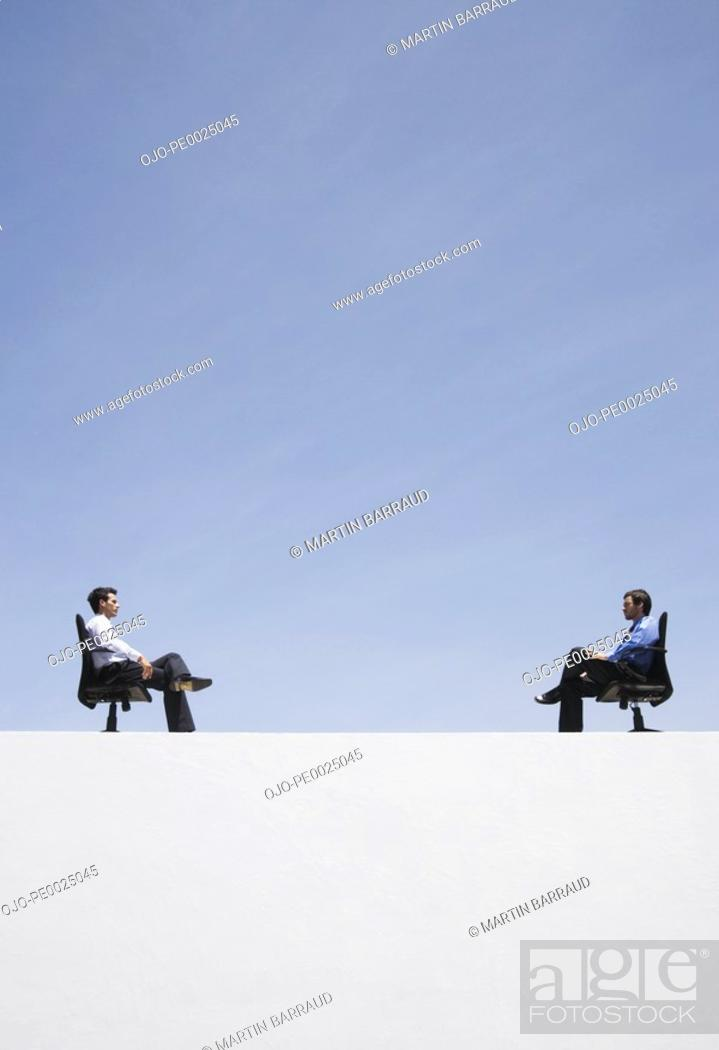 Stock Photo: Two businessmen in office chairs on wall outdoors.