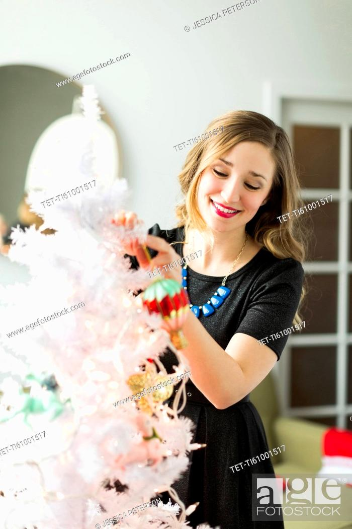 Stock Photo: Young woman holding Christmas ornament.