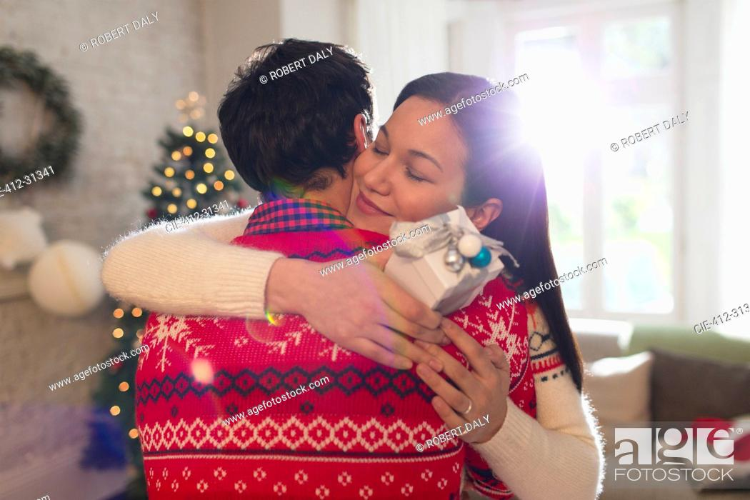Stock Photo: Grateful girlfriend with Christmas gift hugging boyfriend.