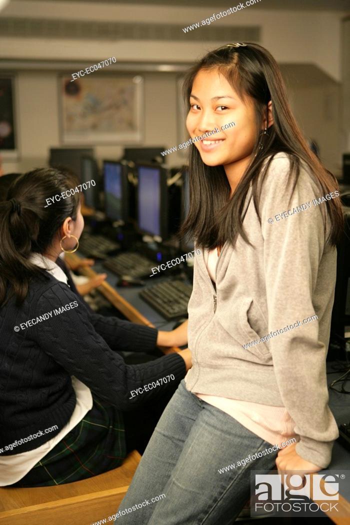 Stock Photo: Teenage girls 15-17 sitting in classroom, portrait.