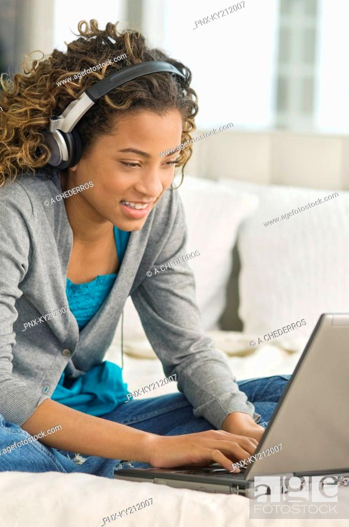 Stock Photo: Girl working on a laptop and listening to headphones.