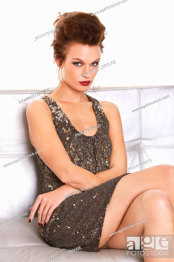 Stock Photo: Young woman in formalwear sitting on sofa.