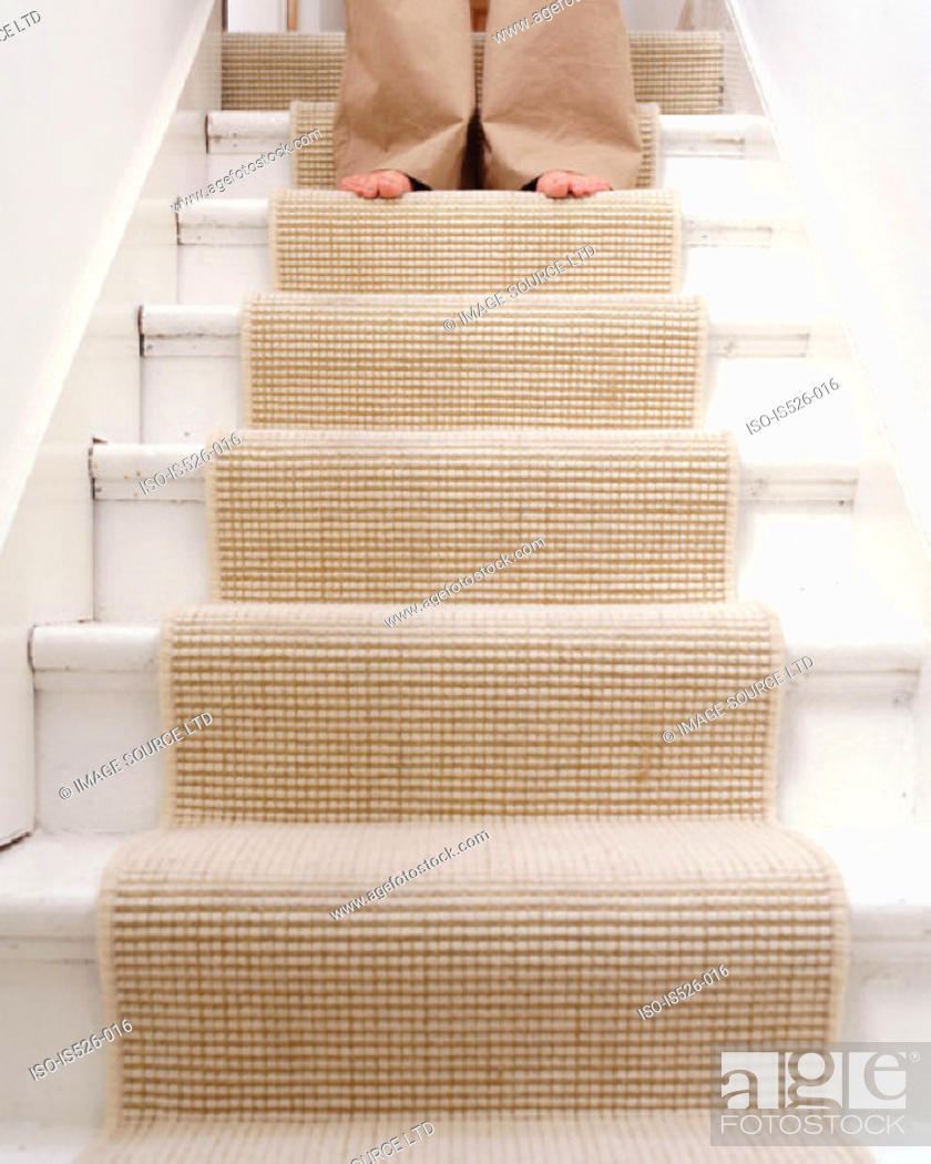 Stock Photo: A female with bare feet coming down the stairs.