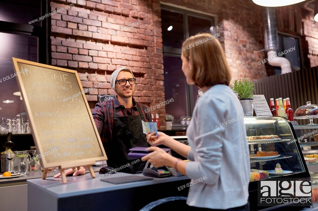 Imagen: small business, payment, people and service concept - happy barman and woman with wallet paying money at cafe.