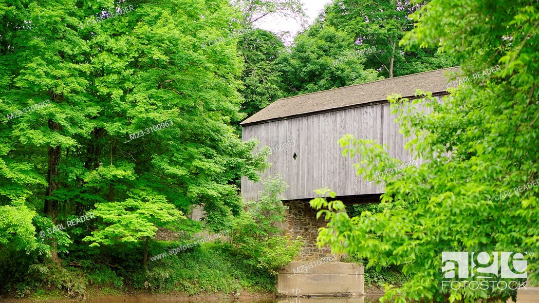 Stock Photo: Trees surround an old wooden covered bridge, Pennsylvania, USA.