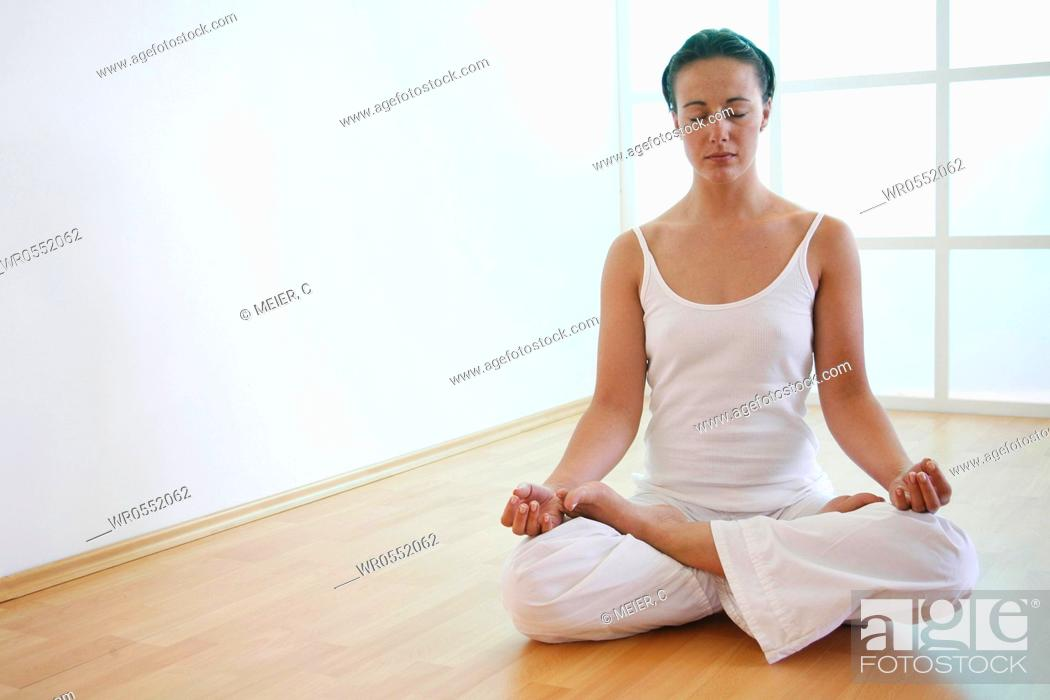 Imagen: Young woman meditates in lotus position on the floor.