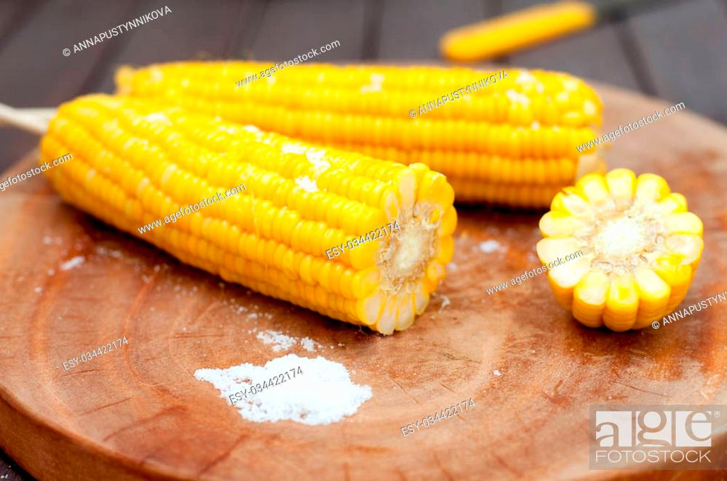 Stock Photo: Boiled sweet corn cobs with salt on a wooden background.