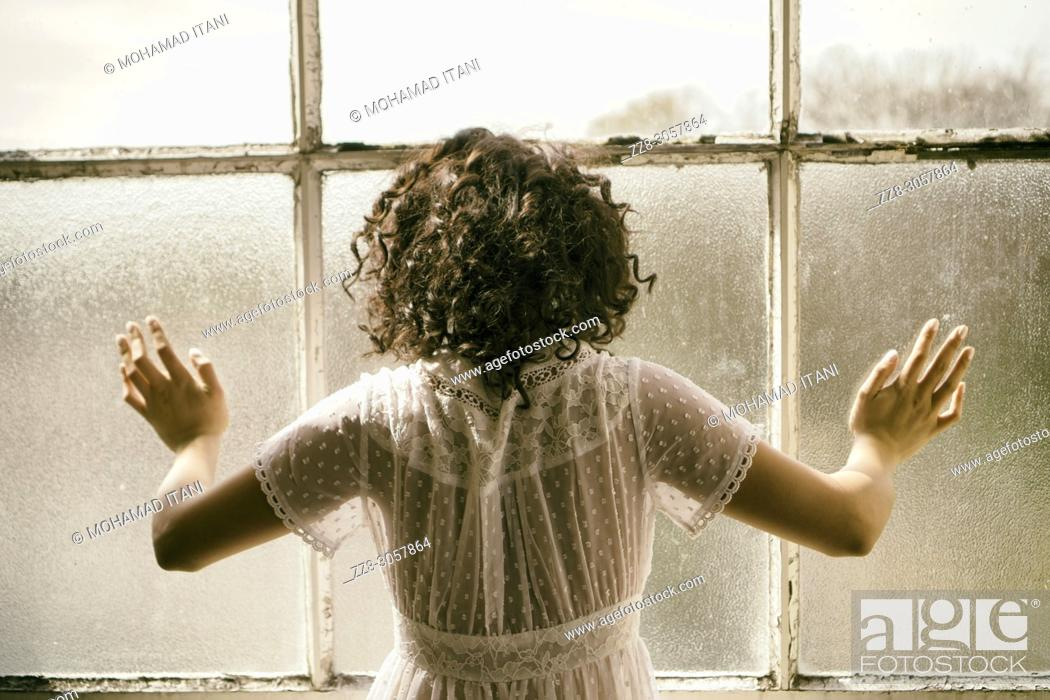 Stock Photo: Rear view of a woman standing by the window hands touching the glass.
