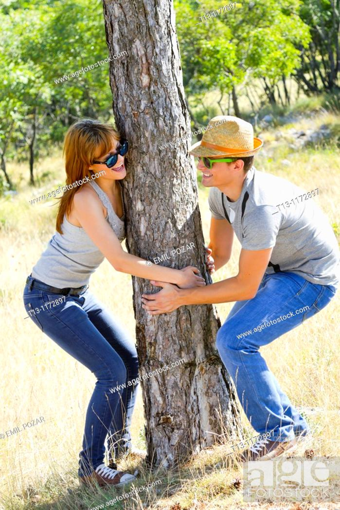 Stock Photo: Playing around a tree girl and boy.