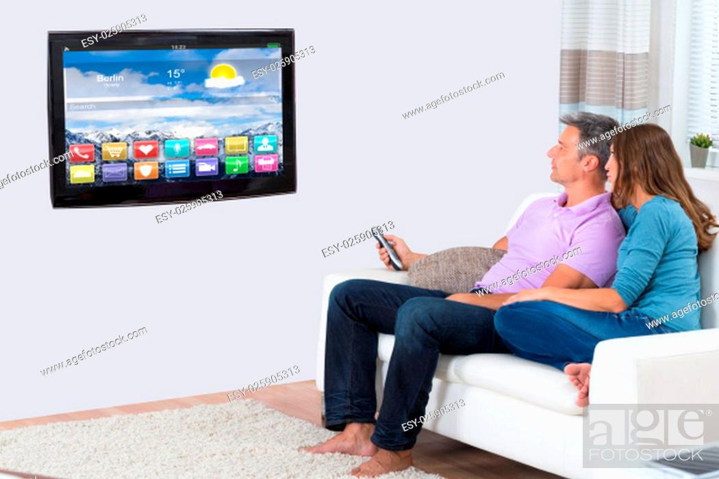 Stock Photo: Couple Sitting On Sofa Watching Television In Living Room.