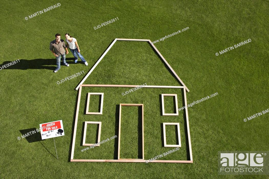 "Stock Photo: Couple standing near ""for sale"" sign and house outline."