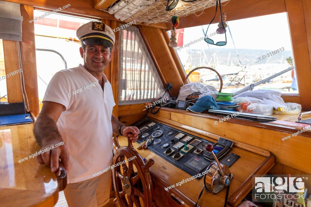 Stock Photo: Captain at steering wheel on yacht/sailboat while boat is in harbour. Bodrum, Turkey.