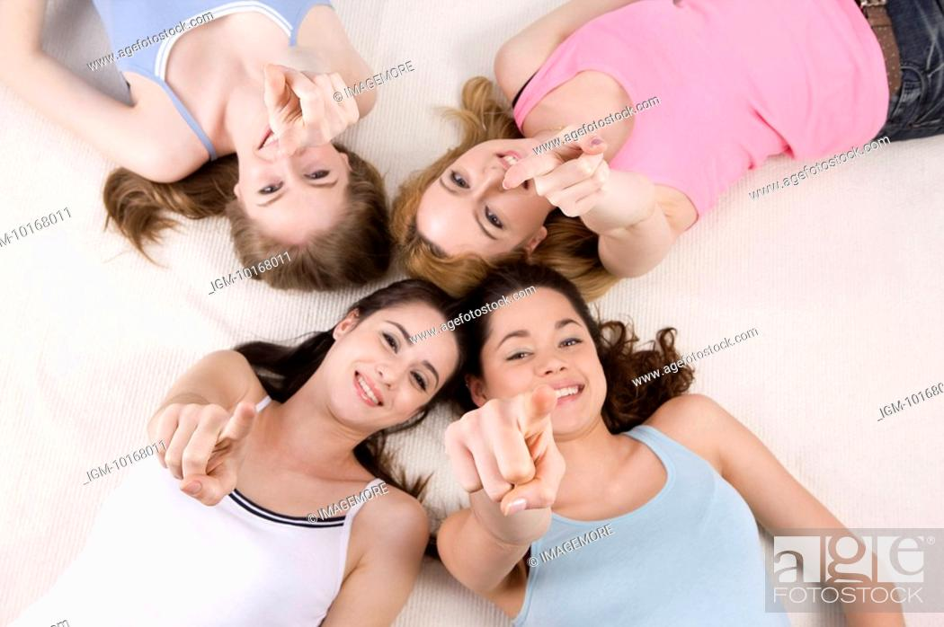 Stock Photo: Four women lying in circle pointing at camera.