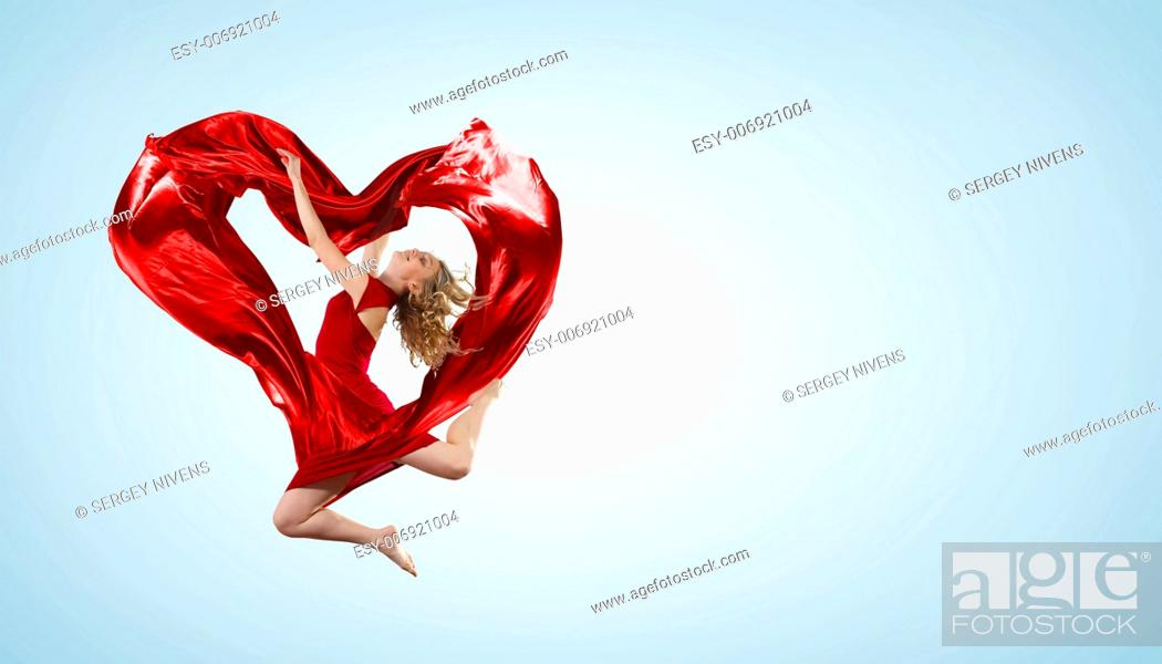 Imagen: Young woman dancing with red fabric in studio and heart symbol.