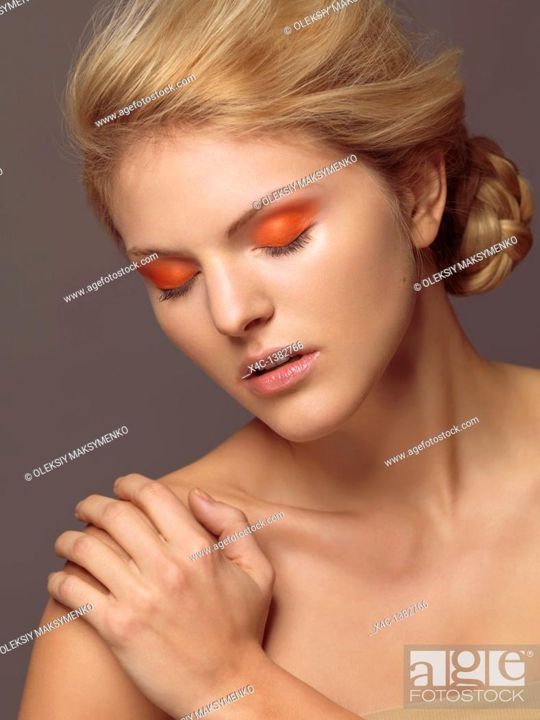 Stock Photo: Beauty portrait of a young woman with bright orange eye shadow.