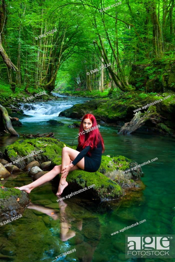 Imagen: Young woman in Green forest sitting near a small river is looking away.