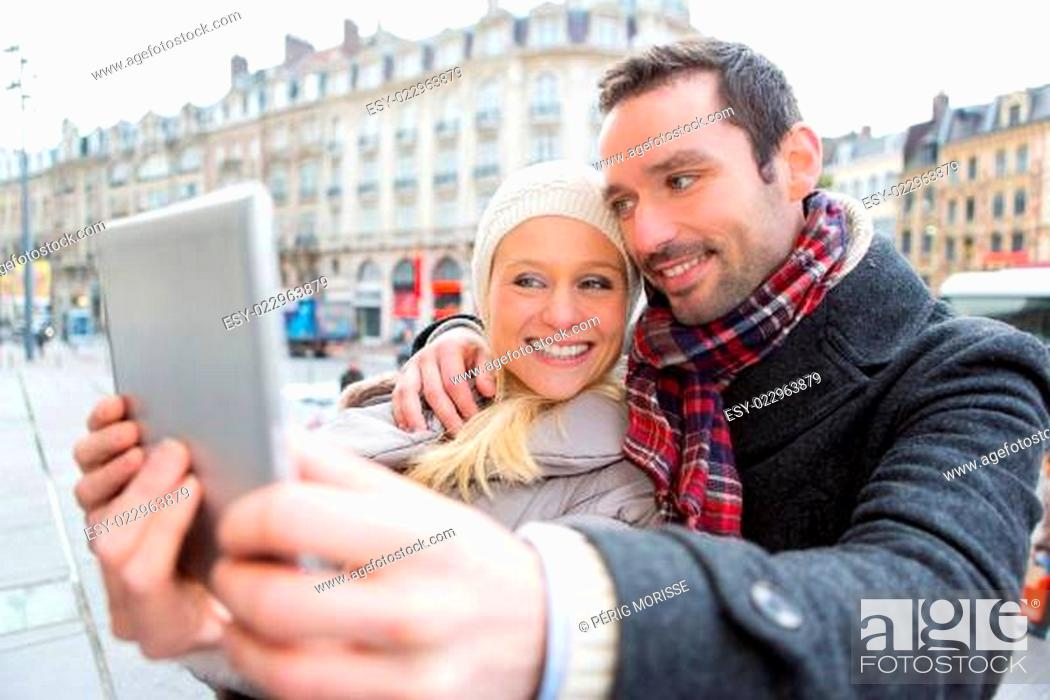 Stock Photo: Young couple on holidays taking selfie.
