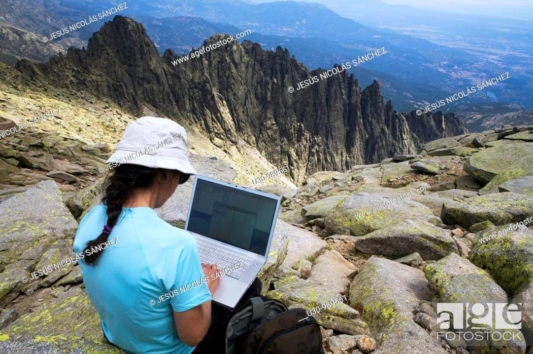 Stock Photo: Woman on the summit of La Mira 2 341 m working with a portable computer  Mountains of the Sierra de Gredos National Park  At the bottom of the image the summits.