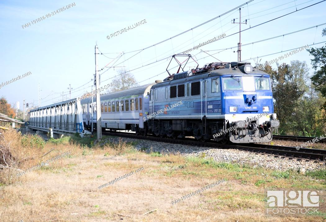 Stock Photo: 15 October 2019, Poland, Küstrin (kostrzyn): An intercity of the Polish state railway PKP passes a level crossing of the city.