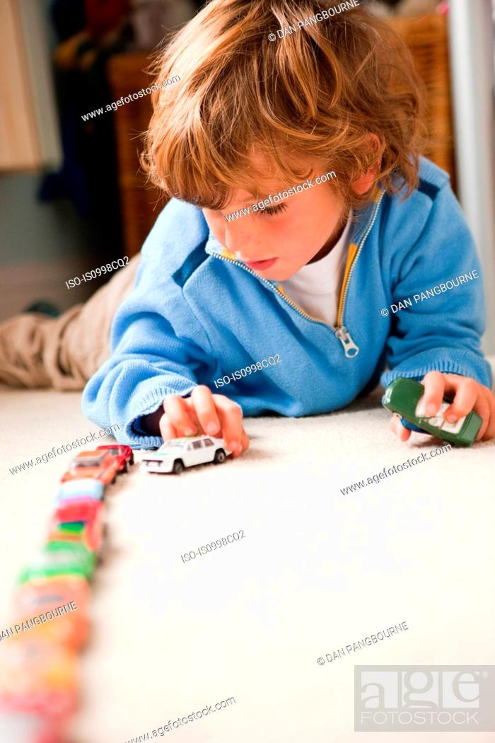 Stock Photo: Young boy lining up toy cars in his bedroom.