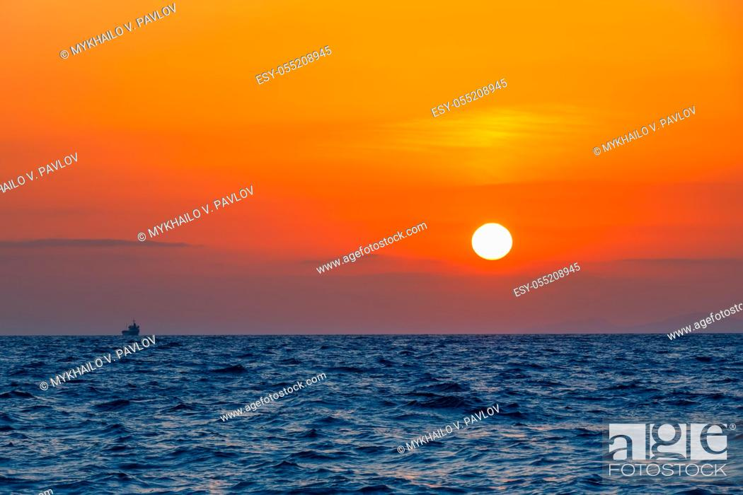 Imagen: Boundless sea. Unbelievable orange sunset. Small freighter ship on the horizon.