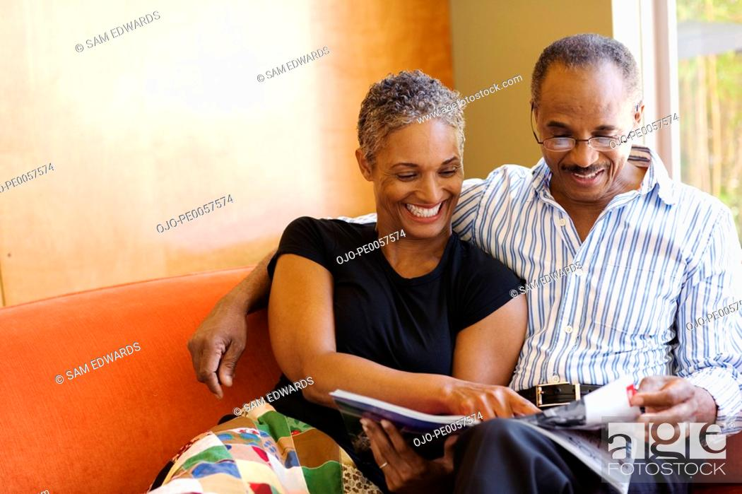 Stock Photo: Couple on sofa in modern home with magazine.