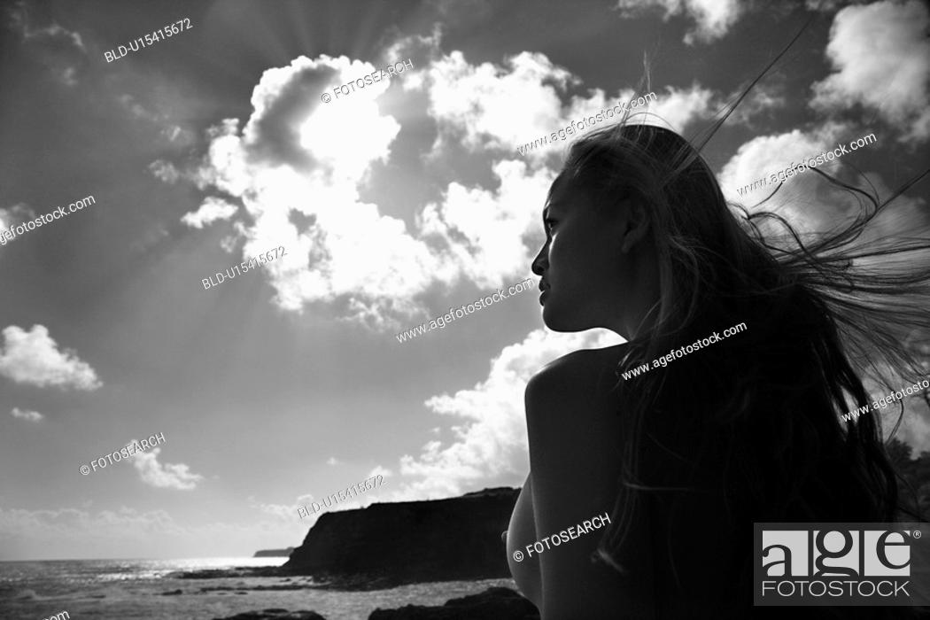 Stock Photo: Young nude woman looking out towards ocean with hair blowing in wind.