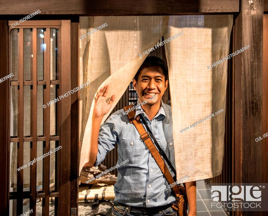 Stock Photo: Man stands at door of traditional Japanese house.