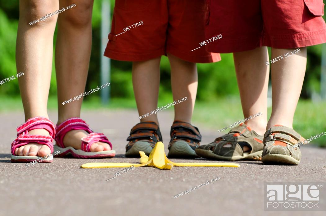 Stock Photo: Children walk on a banana peel on the street.