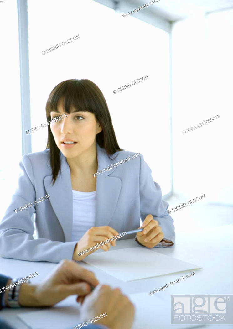 Stock Photo: Businesswoman sitting at table looking attentively toward colleague.