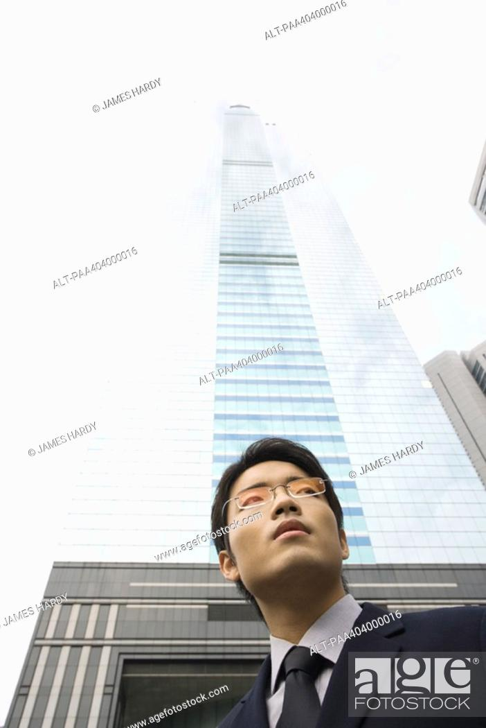 Stock Photo: Young businessman standing in front of skyscraper, low angle view.