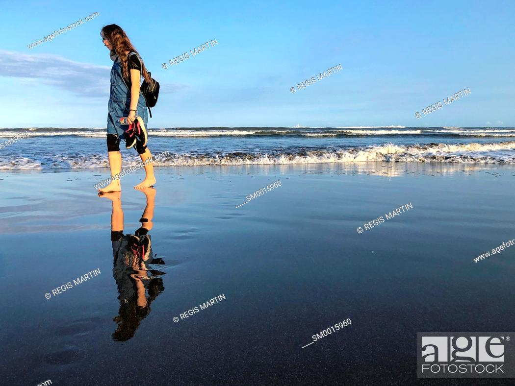 Stock Photo: Young teenage girl walking alone on a beach.