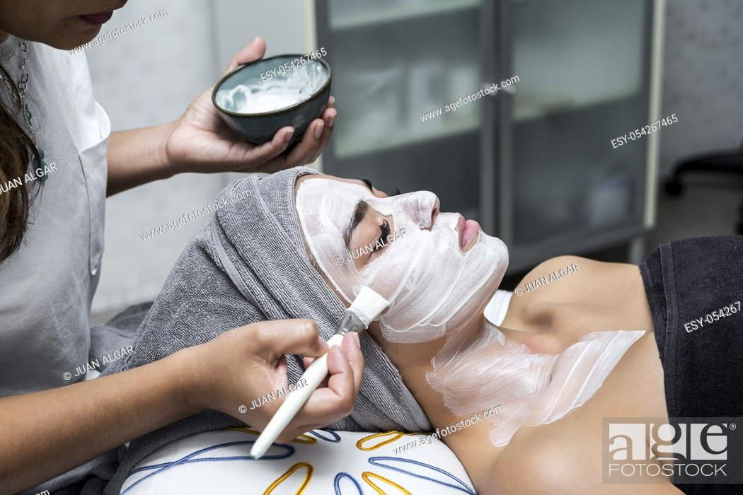 Stock Photo: Crop master applying white mask with brush on face and neck of young woman in towel lying on table.