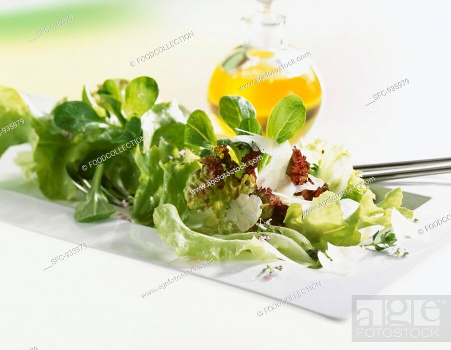 Stock Photo: Mixed salad with Parmesan, bottle of oil in background.