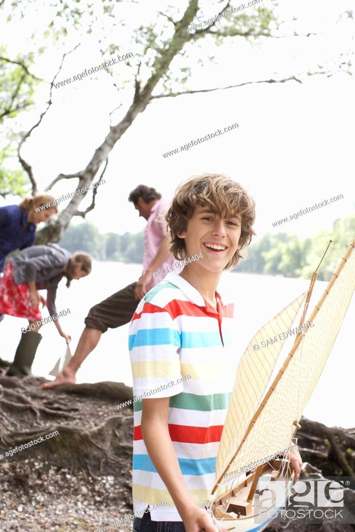 Stock Photo: Boy holding toy sailboat near lake.