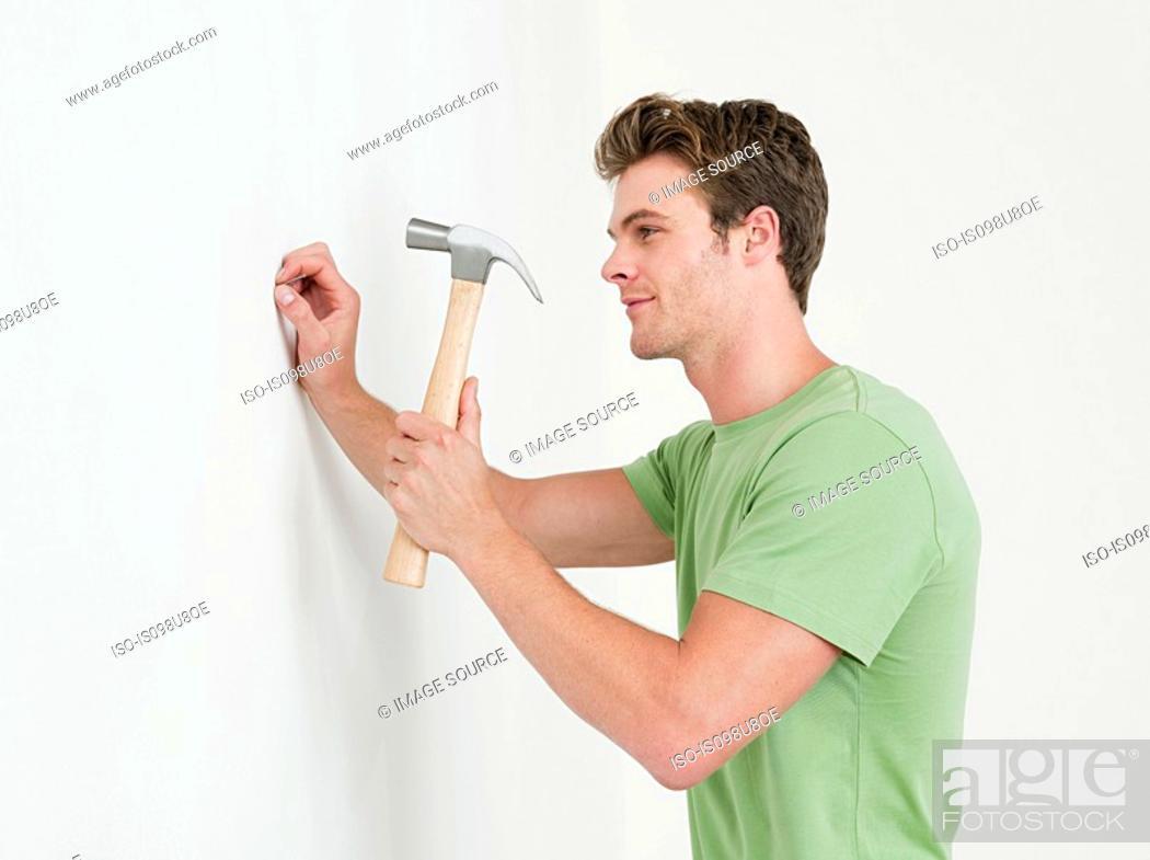 Stock Photo: Young man hammering nail into wall.