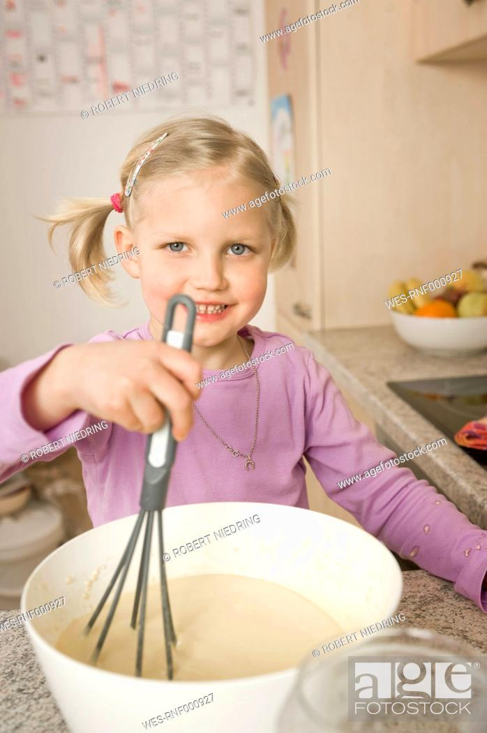 Stock Photo: Girl mixing batter in bowl, smiling, portrait.