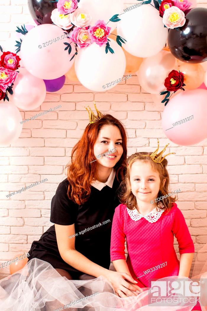 Stock Photo: Two beautiful girls with crowns under birthday balloon and paper flower arch decorations. Childish photozone for celebration. Mom with dauther.
