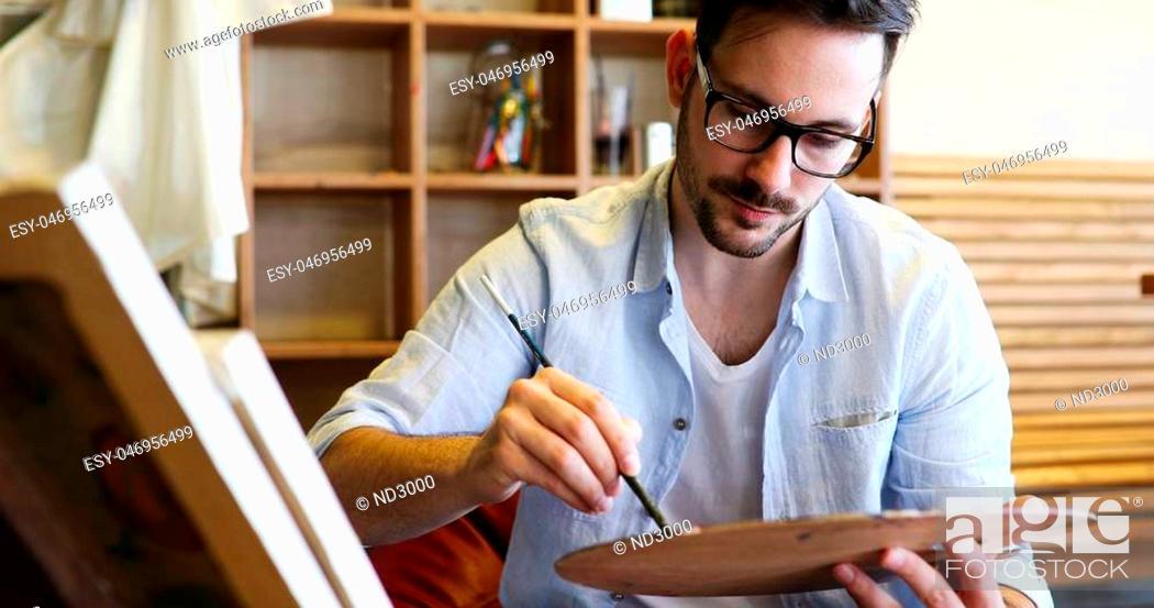Imagen: Male art school artist painting with oil on canvas in studio.