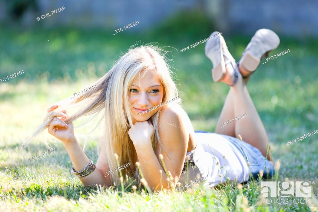 Stock Photo: Attractive young woman portrait happy lying on the grass.