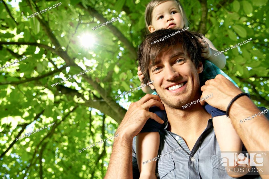 Stock Photo: Germany, Cologne, Father carrying daughter on shoulders, smiling.
