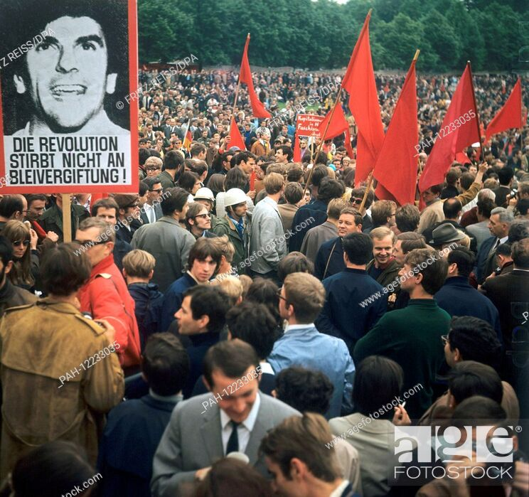 Stock Photo: Students holding red flags protest on 20 May 1968 against the German Emergency Acts. On left a poster of students spokesperson Rudi Dutschke.