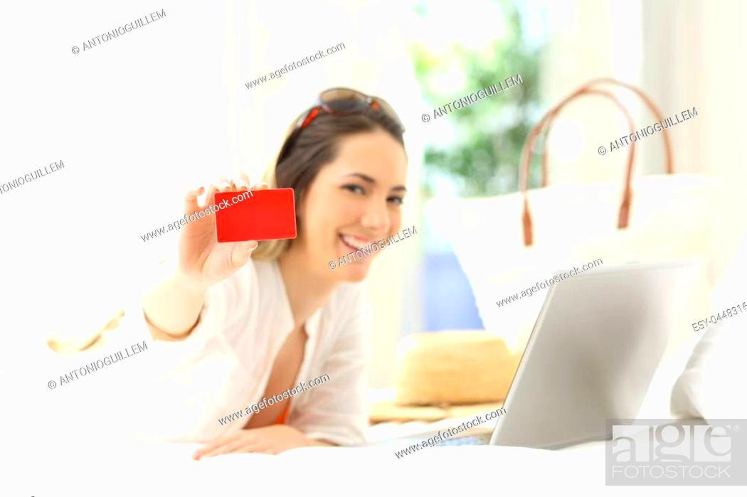 Stock Photo: Woman showing a blank credit card lying on a bed of an hotel room in summer vacations.