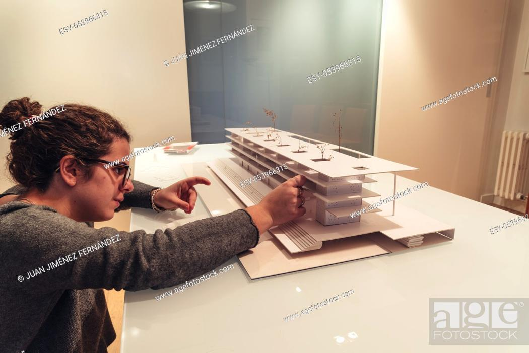 Imagen: Female architect working on architecture model made with cardboard on table in office of architectural firm.