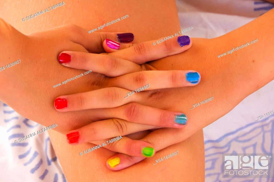 Imagen: Hands of young girl with colors nails.
