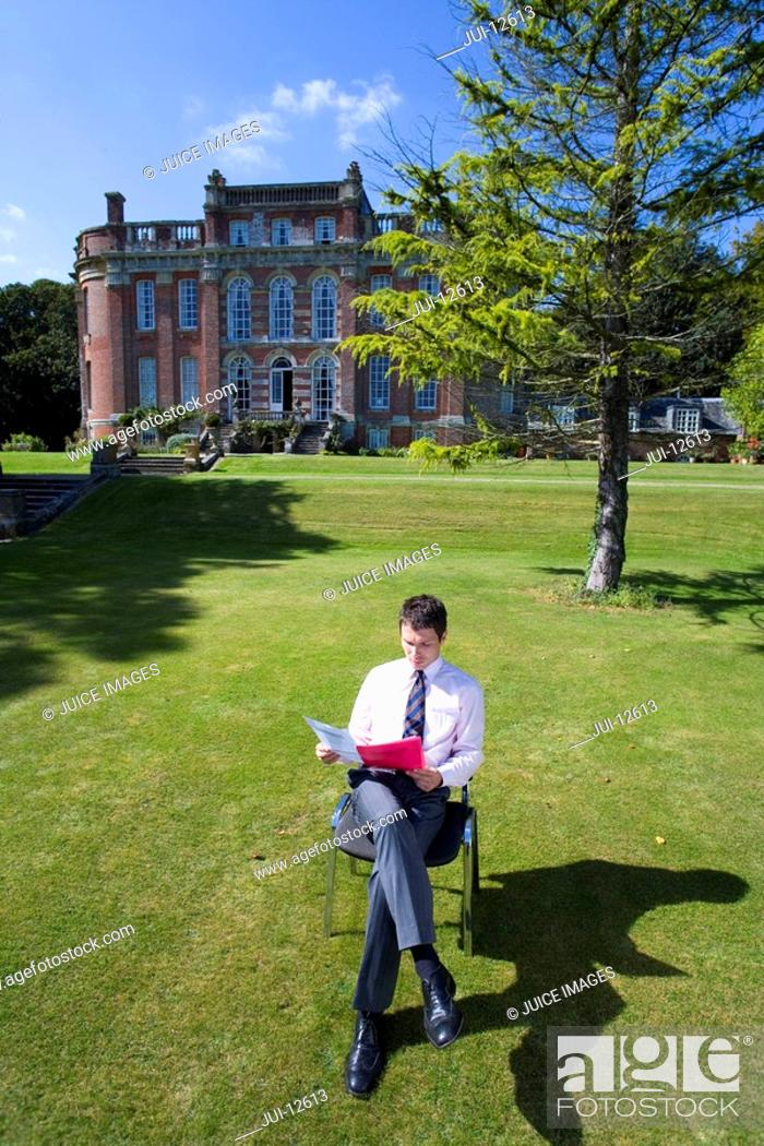 Stock Photo: Businessman with folder by manor house, elevated view.