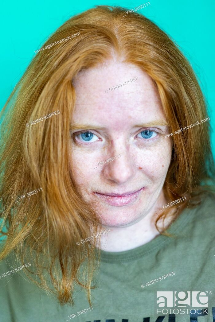 Stock Photo: Tilburg, Netherlands. Studio-portrait of a redhaired woman wearing a branded shirt against a green background.