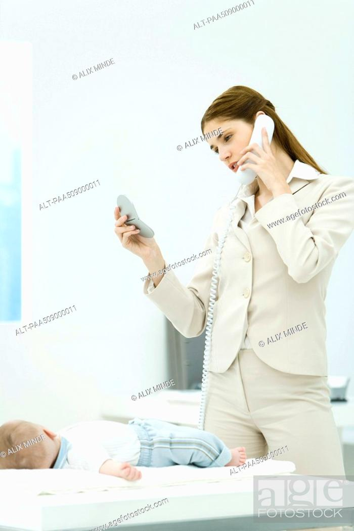 Stock Photo: Professional woman talking on phone, looking at self in mirror compact, baby lying on desk nearby.