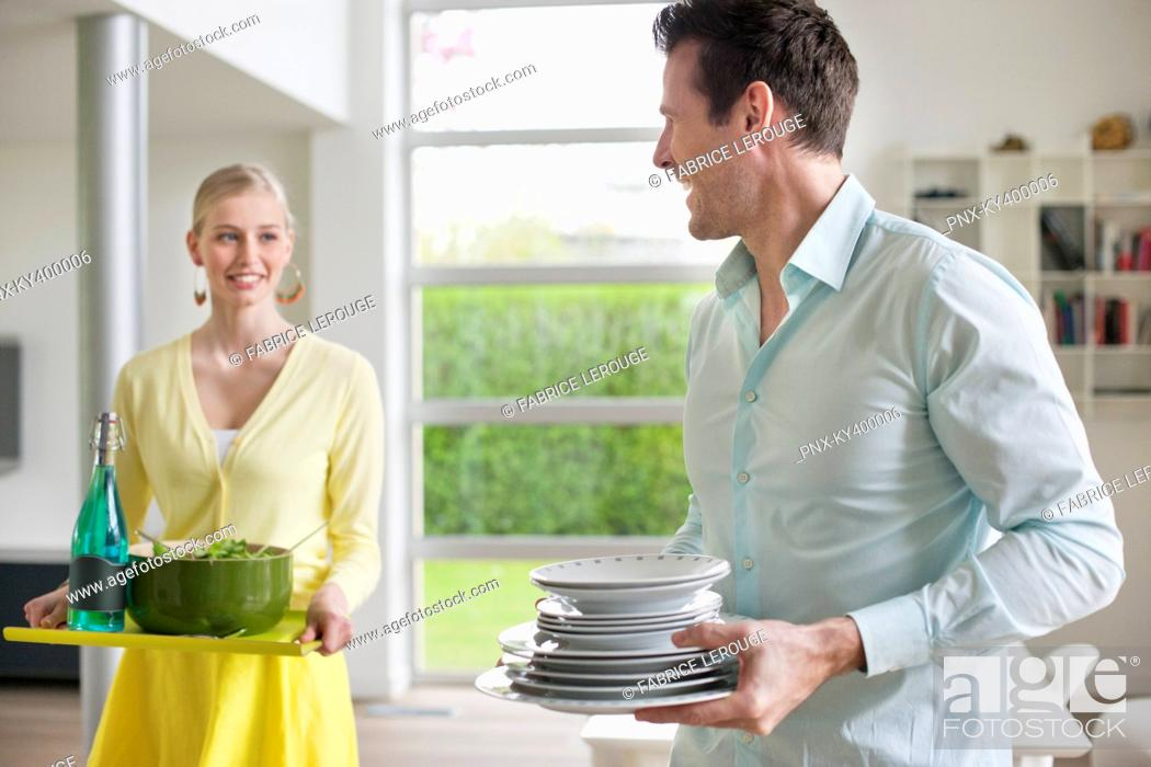 Stock Photo: Couple carrying food and plates for serving.
